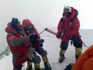 Norbu Zhamdu (L) lights the Olympic torch of the first torchbearer Gegyi with a kindling at the top of the 8844.43-meter summit of Mt. Qomolangma in southwest China's Tibet Autonomous Region on May 8, 2008.