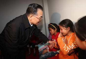 Chinese Premier Wen Jiabao comforts the children who lost their relatives in the powerful earthquake in Mianyang on May 13, 2008.(Xinhua Photo)
