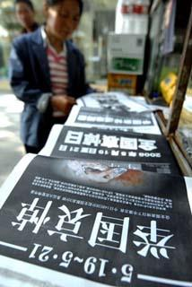 A citizen looks at bold-face front pages of newspapers in Zhengzhou, capital of central China's Henan Province, May 19, 2008.  (Xinhua Photo)