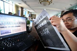 A citizen looks at a newspaper with a bold-face front page in Wuhan, capital of central China's Hubei Province, May 19, 2008.  (Xinhua Photo)
