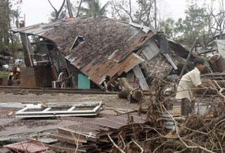A boy plays outside his home which was destroyed by Cyclone Nargis, outside Yangon May 19, 2008.(Xinhua/Reuters Photo)