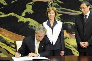 U.S.PresidentGeorgeW.Bush(L)leaveswordsonthebookofcondolenceashiswifeLauraBush(C)andChineseAmbassadortotheU.S.ZhouWenzhonglookonattheChineseEmbassyinWashingtonMay20,2008.BushcametotheChineseEmbassyonMay20tomournChinesequakevictims.(XinhuaPhoto)