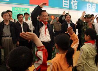 Chinese Premier Wen Jiabao (C) salutes with the students to pay tribute to the quake victims during his visit to the makeshift tent school at Jiuzhou Stadium in Mianyang City, southwest China's Sichuan Province, May 23, 2008. Wen Jiabao went to the temporary schoolhouse of Beichuan Middle School and the makeshift tent school established at Jiuzhou Stadium in Mianyang on Friday to visit teachers and students who survived the May 12 earthquake.(Xinhua Photo)