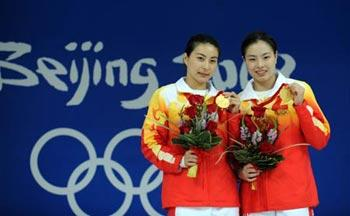 Chinese divers Guo Jingjing (L) and Wu Minxia pose for picture during the awarding ceremony for women's synchro 3m springboard at the Beijing 2008 Olympic Games in the National Aquatics Center, also known as the Water Cube in Beijing, China, Aug. 10, 2008. Guo and Wu claimed the title in the event with a score of 343.50 poionts. (Xinhua/Zhao Peng)