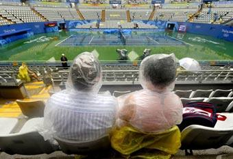 Spectators wait under the rain for the tennis tournament of the 2008 Beijing Olympic Games to begin, at the centre court of the Olympic Green Tennis Centre in Beijing on August 10, 2008.