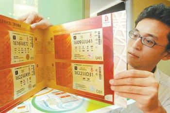 A member of the ticketing sales staff shows some Beijing Olympic commemorative tickets in Beijing, August 27, 2008. A set of 2008 Beijing Olympic Commemorative Tickets is to be issued on September 21 by China Banknote Printing and Minting. [Beijing Stardaily]