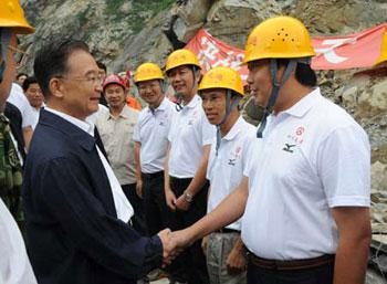 Chinese Premier Wen Jiabao (L) shakes hands with workers while visiting a road repair site near the epicenter, Yingxiu, southwest China's Sichuan Province, Sept. 2, 2008. (Xinhua Photo)