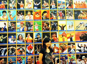 A visitor has a photo taken in front of a wall on which photos of the champions of the Beijing 2008 Olympic Games were shown at the Panoramic Photo Exhibition of the Beijing Olympic Games opened in Beijing Sept. 5, 2008. More than 300 photos taken by Xinhua's photojournalists were shown in the exhibition which was held on a theme of sharing glory and dream.(Xinhua Photo/Xu Jiajun)
