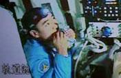 Chinese taikonaut tries bite on his food in Shenzhou-7