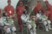 Astronauts exit re-entry capsule