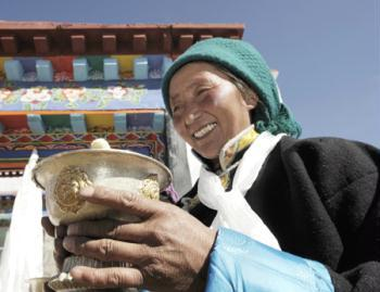 A Tibetan villager toasts during a ceremony for moving into her new house in Kunggar Town of Maizhokunggar County in Lhasa, capital of southwest China's Tibet Autonomous Region, Feb. 11, 2009. Twenty-four families of farmers and herders in Kunggar moved into new houses ahead of Tibetan new year which falls on Feb. 25. Some 312,000 farmers and herders from 57,800 families had moved from shanty homes into new solid brick houses in Tibet in 2008 under a government-subsidized housing project aimed at improving living conditions.(Xinhua/Purbu Zhaxi)