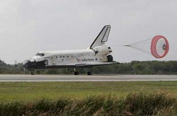 The space shuttle Discovery has its drag parachute deployed as it rolls past the runway convoy after it returned to earth at the Kennedy Space Center in Cape Canaveral, Florida March 28, 2009. The landing ends Mission STS-119 to the International Space Station. (Xinhua/Reuters Photo)