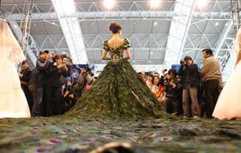 A model presents a wedding dress decorated with peacock feathers at the wedding expo held in Nanjing, capital of east China's Jiangsu Province, March 28, 2009. (Xinhua Photo)
