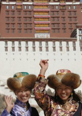 Two women pose for photos in front of the Potala Palace in Lhasa, capital of southwest China's Tibet Autonomous Region, Feb. 11, 2008.  (Xinhua/Chogo)