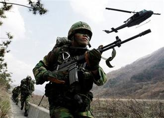 South Korean soldiers run as U.S. Army's Aviation Brigade HU-1 Huey takes off during the U.S.-South Korea joint military exercise in Mungyeong, south of Seoul, South Korea, Tuesday, March 31, 2009.(AP Photo/Lee Jin-man)