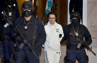 Federal police officers escort Vicente Carrillo Leyva, during his presentation to the media in Mexico City, Thursday, April 2, 2009.(AP Photo/Eduardo Verdugo)