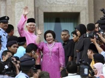 Malaysian new Prime Minister Najib Razak, left in pink, waves with his wife Rosmah Mansor at prime minister's office in Putrajaya, outside Kuala Lumpur, Malaysia, Friday, April 3, 2009. Najib took office Friday, inheriting myriad challenges, including a flagging economy, a racially divided society and a moribund ruling party struggling to regain its popularity.(AP Photo)