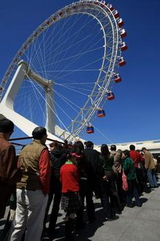 'Tourists queue up to ride the 120-meter-high observation wheel