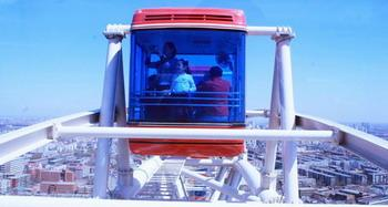 'Tourists take a view from a cabin on the 120-meter-high observation wheel