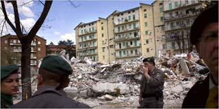Police officers and rescue workers on Tuesday at the ruins of an apartment complex in L'Aquila, Italy. The death toll rose to 235.