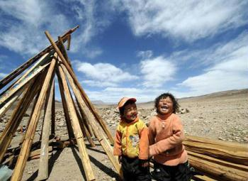 Two children play near the timber for house building at the quake-hit area of Yangyi Village, Geda Town, Damxung County of Lhasa, capital of southwest China's Tibet Autonomous Region, on April 20, 2009. (Xinhua Photo)