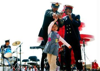 A little girl dances as members of Bangladeshi navy's military band perform during a performance in Qingdao, east China's Shandong Province, April 21, 2009.(Xinhua/Li Gang)