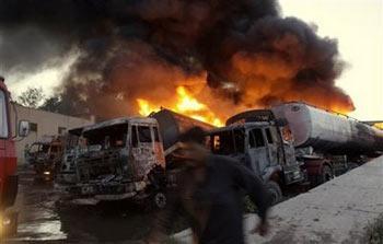 FlamesrisefromNATOterminalafteranallegedmilitants'attackinPeshawar,Pakistan,Thursday,April23,2009.DozensofmilitantsarmedwithgunsandgasolinebombsattackedthetruckterminalinnorthwesternPakistanThursdayandburnedfivetankertruckscarryingfueltoNATOtroopsinAfghanistan,policesaid.(APPhoto/MohammadSajjad)