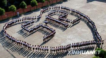Pupils in Leping No.1 Elementary School in Jiangxi Province stand in circle to form a Charriol with 5.12 in it in order to commemorate the Sichuan earthquake on May 12 last year. (Xinhua Photo)
