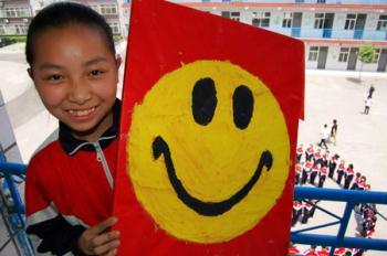 A girl shows a board with a smiling face during an activity to celebrate the upcoming World Smile Day at No. 10 Middle School in Xingtai, north China's Hebei Province, May 7, 2009. The World Smile Day falls on May 8. (Xinhua/Chen Lei)