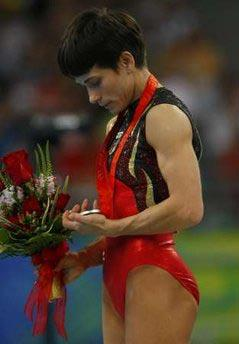 SilvermedallistOksanaChusovitinaofGermanylooksathermedalduringthemedalpresentationceremonyforthegymnasticswomen'svaultfinalattheBeijing2008OlympicGames.