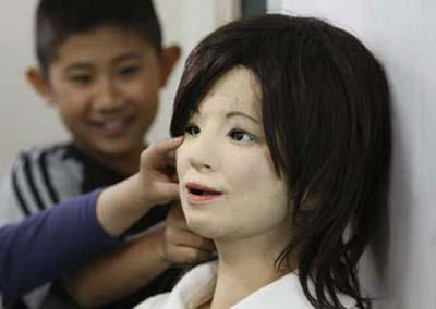 "A humanoid robot named ""Saya"" (R) is touched by school pupils as she takes on a role as a school teacher during a demonstration at an elementary school in Tokyo May 7, 2009. The robot, developed by Tokyo University of Science professor Hiroshi Kobayashi, can speak different languages and make facial expressions like happiness, surprise, sadness, fear, anger or disgust with motors inside her face. (Xinhua/Reuters Photo)"