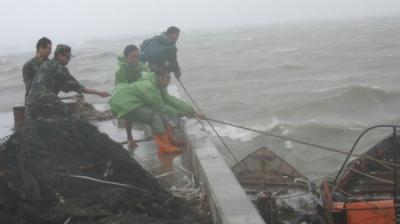 SoldiershelpfastenfishingboatsinZhangzhou,eastChina'sFujianprovince,astheChina'ssoutheastcoastbracesfortropicalstormLinfaonSunday,June21,2009.[Xinhua]