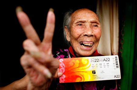 Xiao Xincui, 98, gestures with a Beijing Olympic ticket while sitting on her tricycle in Beijing on August 6, 2008. Her grandson, Liu Xianghui, has taken her to watch the Olympics by riding the tricycle from Hunan Province. [Photo: Rednet.cn]