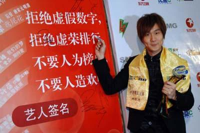 Singaporean Wayne Lin Junjie, a pop singer high on the top 5 of the grand Chinese pops by the 16th Oriental Wind and Cloud Music Rankings, one of the most influential pop music ranking for lyrics in Chinese on Chinese mainland, puts signature on the board with epigram reminder for pop singers' virtues, during the awarding ceremony held in east China's Shanghai Municipality, March 15, 2009. The awards of best male and female pop singers are presented to Sun Nan and Zhang Liangying of Chinese mainland. (Xinhua Photo)