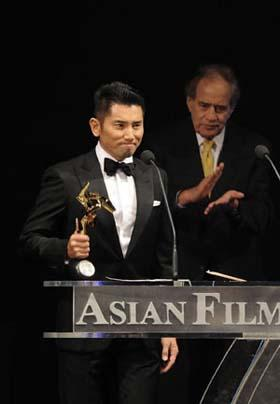 Japanese actor Motoki Masahiro (L) gives acceptance speech afer receiving for Best Actor of the 3rd Asian Film Awards at the Hong Kong Convention and Exhibition Center in south China's Hong Kong, Mar. 23, 2009.(Xinhua Photo)