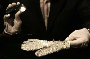 An assistant shines a flashlight on Michael Jackson's white crystal-covered glove in Beverly Hills, California April 13, 2009. Items from the life and career of the pop star will be auctioned from April 22-25.(Xinhua/Reuters Photo)