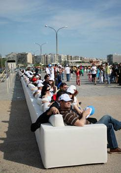 People sit on a super-long sofa in Thessaloniki, Greece, May 9, 2009. This 64.75-meter-long sofa set the Guinness World Records for being the longest sofa in the world. (Xinhua/AFP photo)