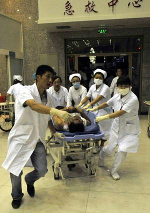 An injured man is carried to an urgent care center in Urumqi, capital of northwest China's Xinjiang Uygur Autonomous Region on July 5, 2009.(Xinhua/Shen Qiao)