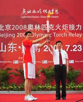 The Olympic torch was relayed in Jinan, capital city of Shandong Province on July 23, 2008. The first torchbearer Gong Xiaobin (L) receives the torch at the launching ceremony.(Xinhua Photo)