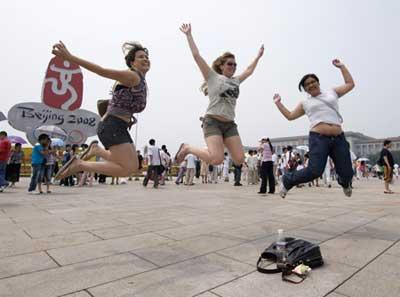 Brazilian tourists (L-R) Rayana Ueda, Tarsila Arruda and Silvia Lei jump in front of a 2008 Olympic sign in Beijing's Tiananmen Square on August 5, 2008. The tourists from San Paulo were being photographed by a friend. [Agencies]