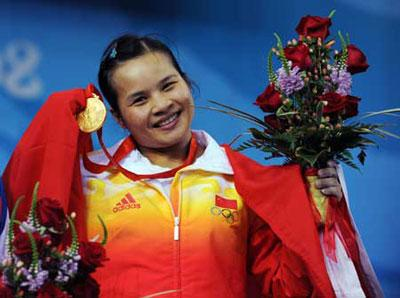 Gold medalist Chen Xiexia of China shows the gold medal at the awarding ceremony of the women's 48kg weightlifting event at Beijing 2008 Olympic Games at the Beijing University of Aeronautics & Astronautics Gymnasium in Beijing, China, Aug. 9, 2008. Chen won the first gold for the Chinese Delegation with a total of 212 kilos. (Xinhua/Yang Lei)