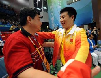 Pang Wei (R) of China celebrates with his coach Wang Yifu after men's 10m air pistol final of Beijing Olympic Games at Beijing Shooting Range Hall in Beijing, China, Aug. 9, 2008. Pang Wei won the gold medal in men's 10m air pistol final. (Xinhua/Jiao Weiping)