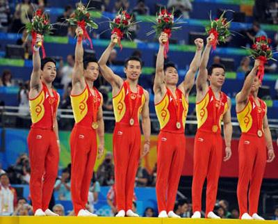 China's Zou Kai, Yang Wei, Xiao Qin, Li Xiaopeng, Huang Xu and Chen Yibing (L-R) wave to spectators on the podium during the awarding ceremony for gymnastics artistic men's team competition of the Beijing 2008 Olympic Games at National Indoor Stadium in Beijing, China, Aug. 12, 2008. The Chinese team won the gold medal of the event with 286.125 points. (Xinhua/Wang Lei)