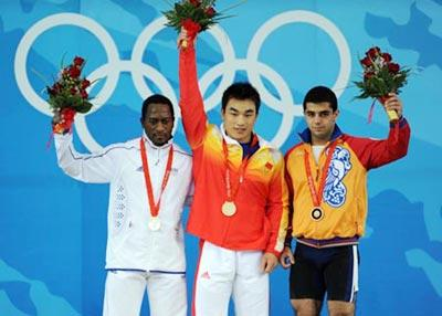 Gold medalist Liao Hui (C) of China, silver medalist Vencelas Dabaya-Tientcheu(L) of France, and bronze medalist Tigran Gevorg Martirosyan of Armenia stand on the podium at the awarding ceremony of the men's 69kg final of weightlifting at Beijing 2008 Olympic Games in Beijing, China, Aug. 12, 2008.(Xinhua Photo)