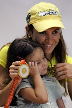 Olympic long jump gold medallist Brazilian Maurren Higa Maggi (R), shows her medal next to her daughter Sophia during a press conference upon her arrival from the Beijing Olympic Games, in Sao Paulo, Brazil, on August 26, 2008. Maggi became the first Brazilian female athlete to win an olympic gold medal in an individual competition. [Agencies]