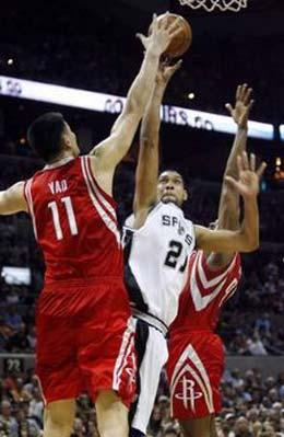 Houston Rockets Yao Ming (L) and Ron Artest (R) defend San Antonio Spurs Tim Duncan during the second half of their NBA basketball game in San Antonio, Texas March 22, 2009.REUTERS/Joe Mitchell (UNITED STATES SPORT BASKETBALL)