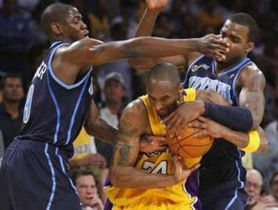 Los Angeles Lakers' Kobe Bryant (C) fights past the defense of Utah Jazz's Ronnie Brewer (L) and Paul Millsap during the second half of Game 2 of their NBA Western Conference quarter-final basketball playoff game in Los Angeles, April 21, 2009. REUTERS/Lucy Nicholson (UNITED STATES SPORT BASKETBALL)