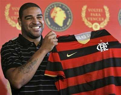 Brazilian soccer player Adriano holds up a Flamengo's jersey during a press conference in Rio de Janeiro, Thursday, May 7, 2009. Adriano was officially introduced by Flamengo, saying he regained his happiness in Brazil and assuring he didn't try to trick Inter Milan into releasing him after he deserted the Italian club.(AP Photo/ Ricardo Moraes)