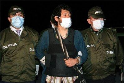 In this photo released by the Colombian National Police, Miguel Angel Beltran, alias 'Jaime Cienfuegos,' center, an alleged member of the Revolutionary Armed Forces of Colombia, FARC, is escorted by police officers upon his arrival to Bogota, Thursday, May 23, 2009. Beltran was arrested in Mexico and extradited to Colombia by the Mexican government.(AP Photo/Colombian National Police)